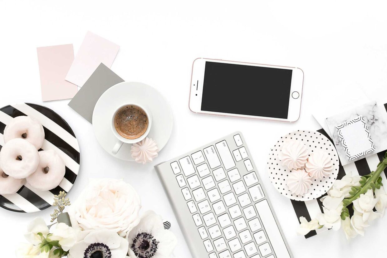 Table assortment with coffee, sweets and tech.
